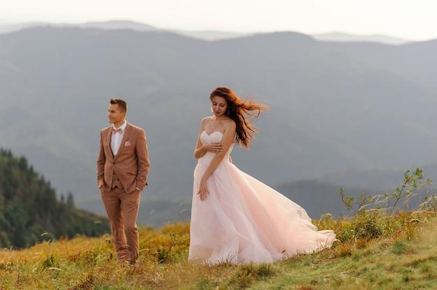 Gli sposi sono vicini l'uno all'altro sullo sfondo delle montagne autunnali.