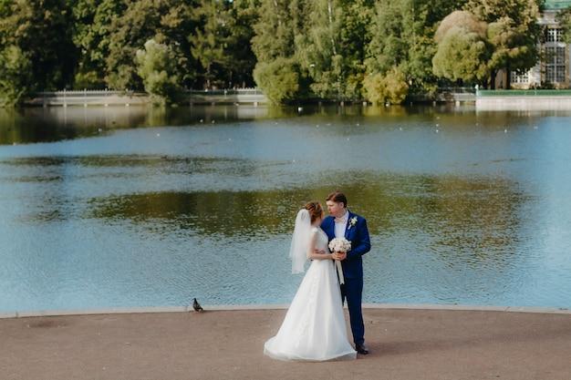 Gli sposi stanno camminando vicino al lago