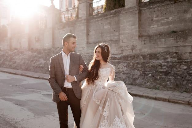 Gli sposi stanno su una vecchia piazza in un giorno soleggiato
