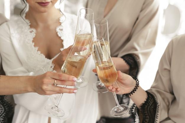 Gli sposi tengono bicchieri di cristallo pieni di champagne