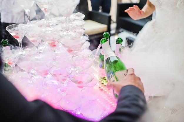 Gli sposi versano champagne nei bicchieri in uno scivolo di champagne