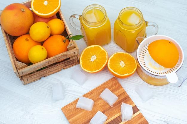 Gli spremiagrumi arancioni due bicchieri di succo d'arancia una scatola di legno riempita di arancia su superficie bianca