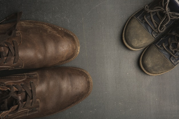 Gli stivali del papà e le scarpe del bambino, concetto di festa del papà.
