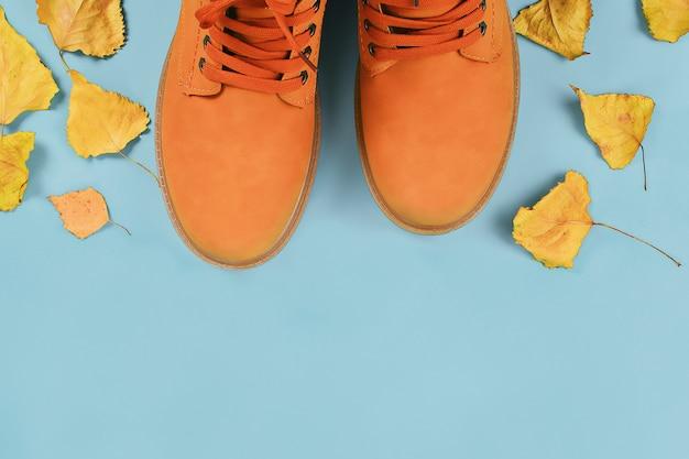 Gli stivali di autunno degli uomini di marrone arancio su pastello grigio. vista dall'alto, copia spazio.
