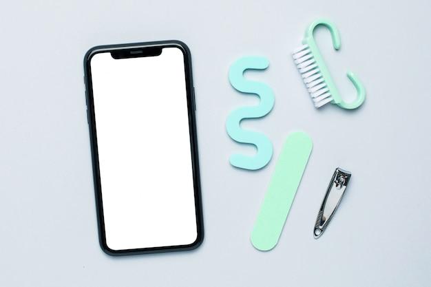 Gli strumenti del manicure e il telefono cellulare di pedicure deridono su su fondo blu