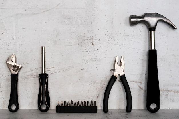 Gli strumenti di costruzione si trovano su uno sfondo di cemento chiaro.