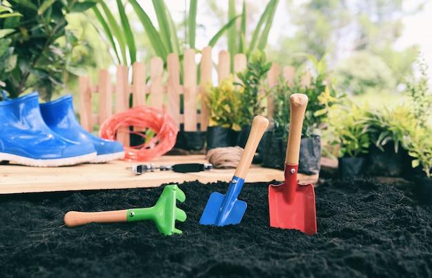 Gli strumenti di giardinaggio sul fondo del suolo pronti a piantare i fiori e la piccola pianta in primavera fanno il giardinaggio di concetto degli impianti di giardino