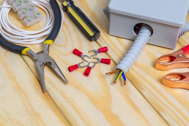 Gli strumenti e gli accessori utilizzati nell'installazione elettrica o nella riparazione sul tavolo di legno dell'officina