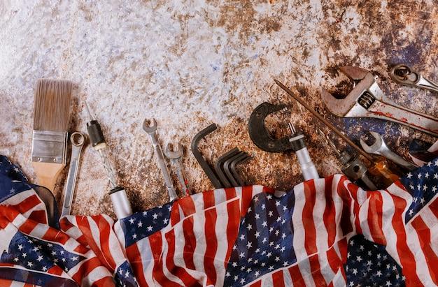 Gli strumenti per la costruzione di chiavi inglesi su una bandiera degli stati uniti d'america nella festa del lavoro sono una festa federale
