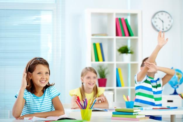 Gli studenti, alzando la mano in classe