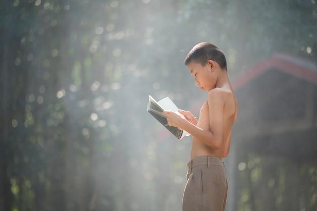 Gli studenti asiatici che leggono i libri nella campagna della tailandia, bambini rurali stanno leggendo un libro