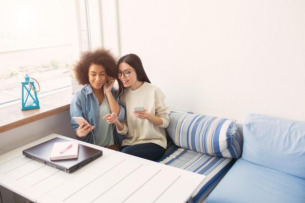 Gli studenti attraenti sono seduti al tavolo e ascoltano musica insieme. stanno condividendo le cuffie tra loro e stanno guardando al telefono. le ragazze sono felici
