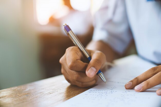 Gli studenti che scrivono la penna in mano facendo gli strati di risposta agli esami si esercitano in aula con lo stress.