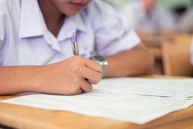Gli studenti della scuola che prendono la scrittura dell'esame rispondono in aula con lo sforzo