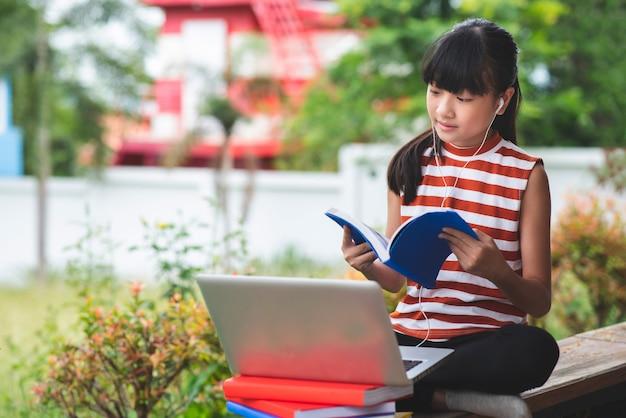 Gli studenti delle scuole elementari in asia siedono e studiano a distanza da casa concetto di istruzione online