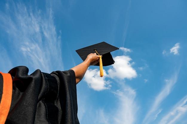 Gli studenti in possesso di un colpo di cappello di laurea per mano in un cielo luminoso