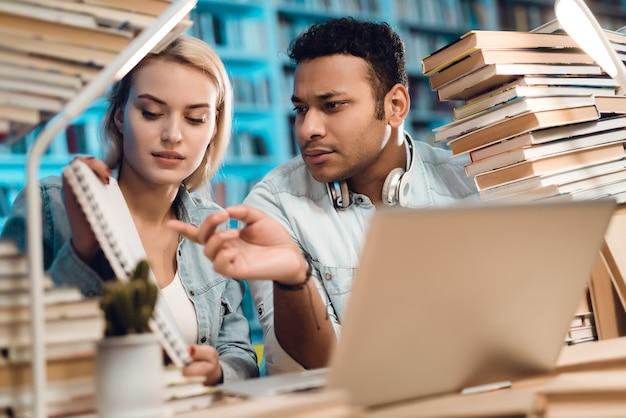 Gli studenti stanno guardando le note in biblioteca