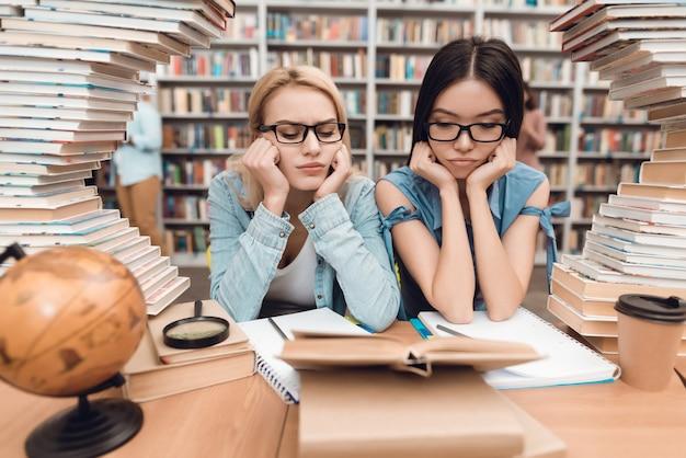 Gli studenti stanno leggendo il libro stanco nella biblioteca scolastica.