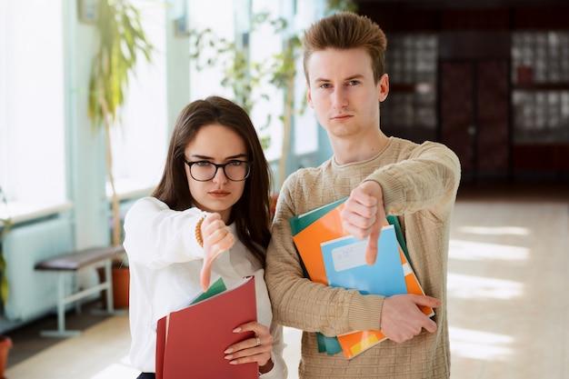 Gli studenti universitari non sono soddisfatti mostrando il pollice verso il basso
