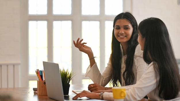 Gli studenti universitari sono seduti insieme davanti a un computer portatile alla scrivania.
