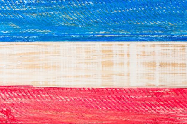 Gli sua rossi e blu hanno dipinto la bandiera sulla plancia di legno per la festa dell'indipendenza