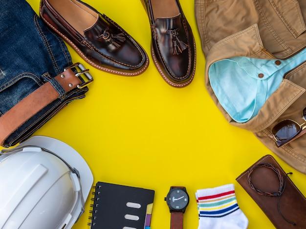 Gli uomini adattano l'insieme e gli accessori dell'abbigliamento isolati su un giallo. ingegnere vestiti concetto, vista dall'alto