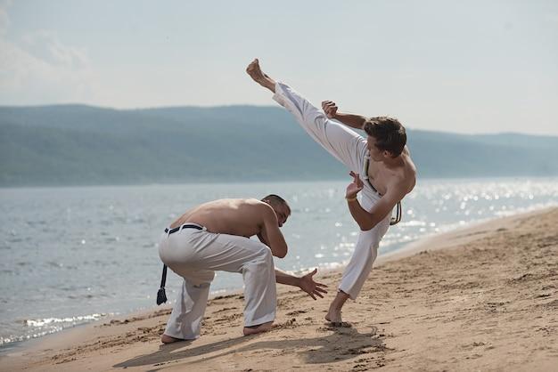 Gli uomini addestrano la capoeira sulla spiaggia - concetto di persone, stile di vita e sport.