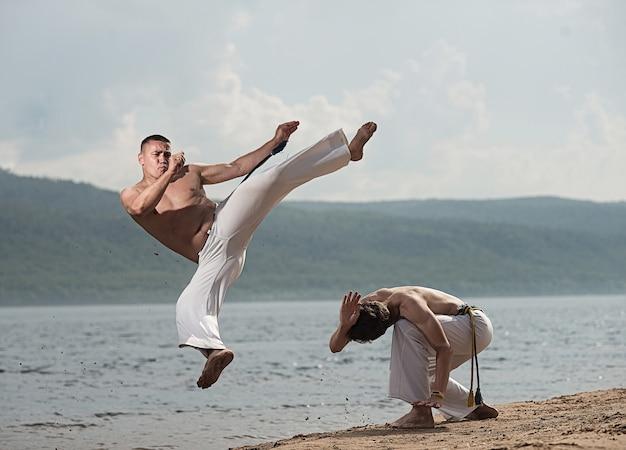 Gli uomini allenano la capoeira sulla spiaggia