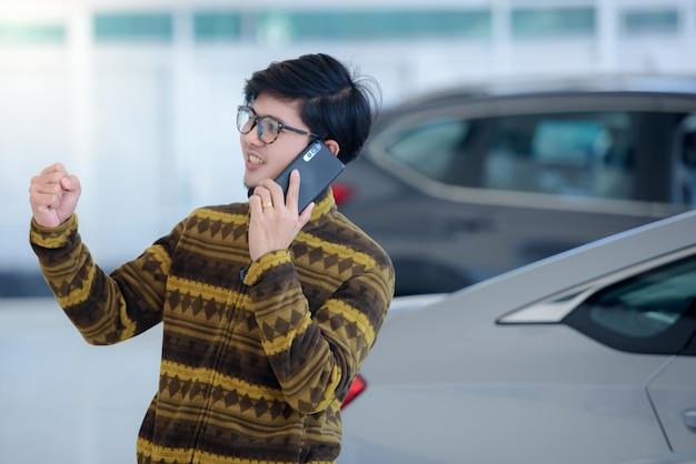 Gli uomini asiatici belli sono felici di acquistare una nuova auto nello showroom, felici mentre parlano al telefono, entusiasti delle buone notizie online nello showroom.
