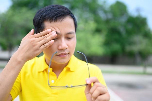 Gli uomini asiatici indossano magliette gialle con stress, affaticamento degli occhi.
