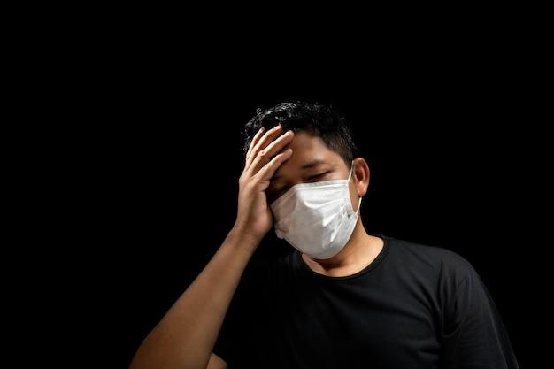 Gli uomini asiatici indossano maschere per prevenire l'influenza, con mal di testa