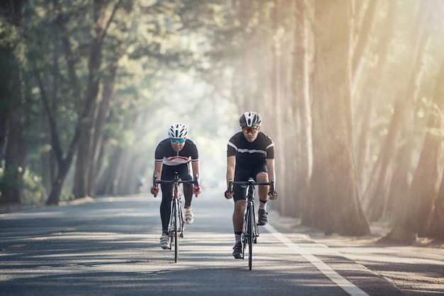 Gli uomini asiatici stanno pedalando in bici da strada al mattino
