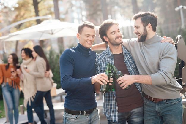 Gli uomini bevono birra durante un picnic con gli amici.