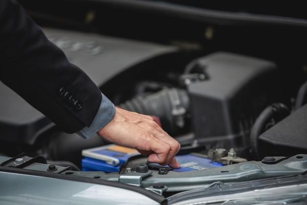 Gli uomini d'affari aiutano le donne d'affari a controllare e riparare le auto rotte