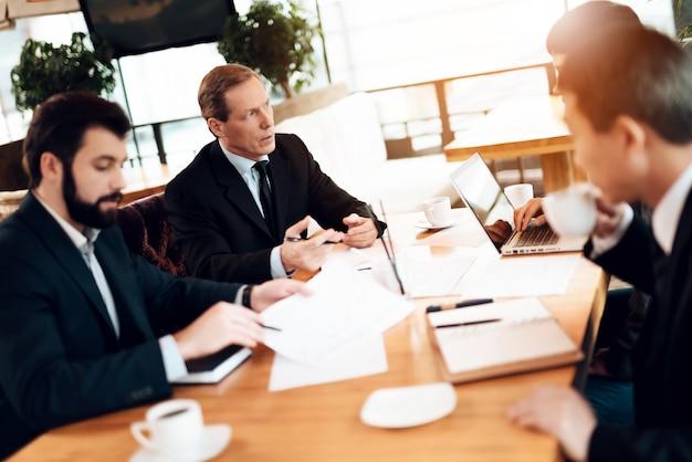 Gli uomini d'affari al tavolo discutono di problemi aziendali