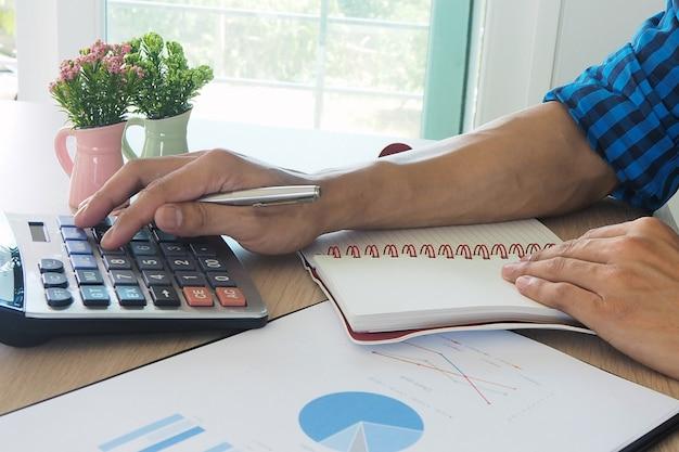 Gli uomini d'affari asiatici lavorano con calcolatrici per calcolare le informazioni sull'account.