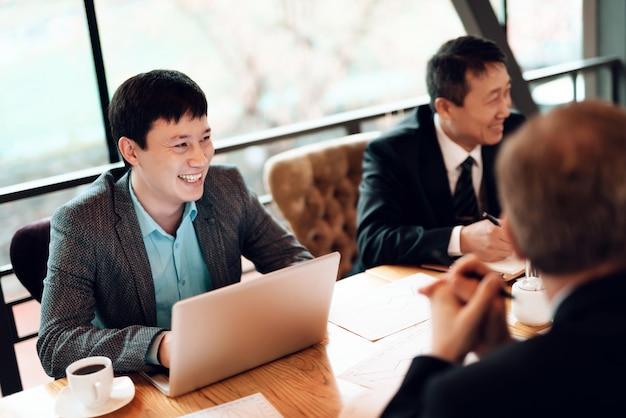 Gli uomini d'affari bevono il caffè in un ristorante e scelgono i piatti