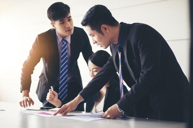 Gli uomini d'affari che lavorano e punto sul diagramma finanziario del grafico e documenti di analisi sulla tavola dell'ufficio