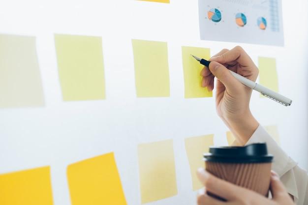 Gli uomini d'affari che si incontrano e usano post-it per condividere l'idea.