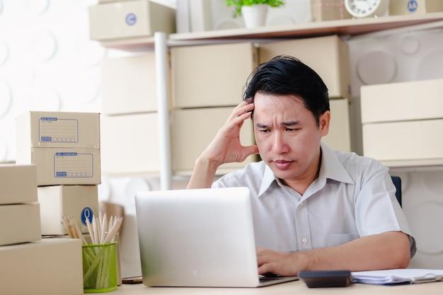 Gli uomini d'affari che si siedono nell'ufficio che guardano il computer portatile dello schermo sono seri, piccola impresa della pmi