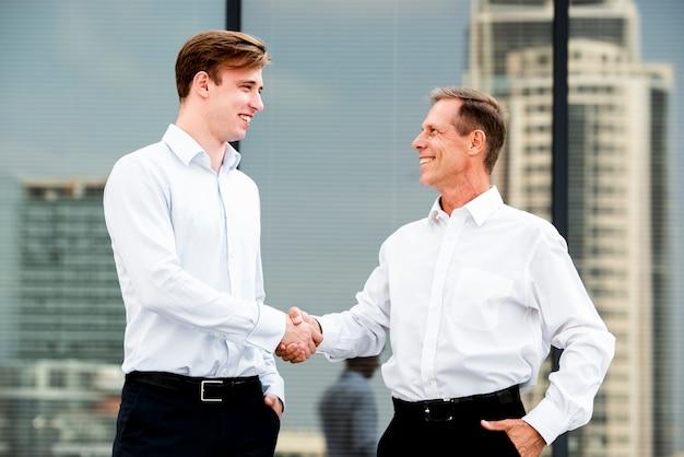 Gli uomini d'affari che stringono le mani si avvicinano alla costruzione di vetro