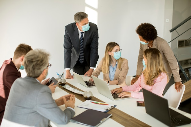 Gli uomini d'affari del gruppo hanno una riunione e lavorano in ufficio e indossano maschere come protezione dal virus corona