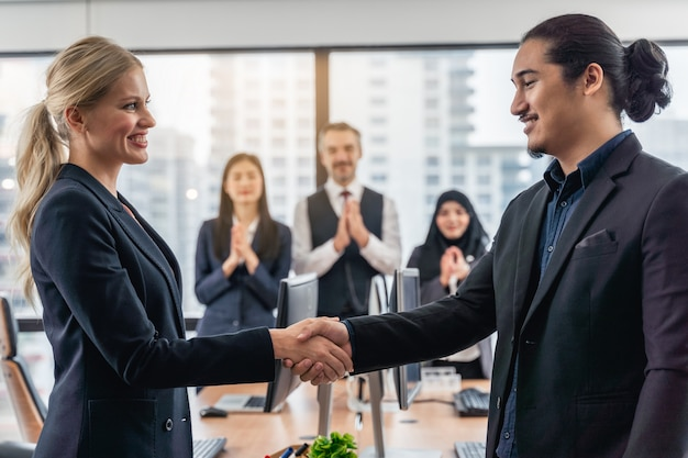 Gli uomini d'affari e la donna di affari che stringono le mani nel corso di una riunione con raggiungono un accordo per l'affare, stretta di mano che gesturing il concetto di affare del collegamento della gente