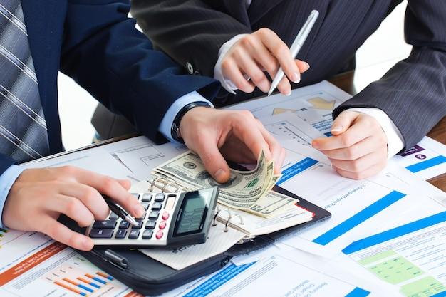 Gli uomini d'affari fanno affari in ufficio al tavolo