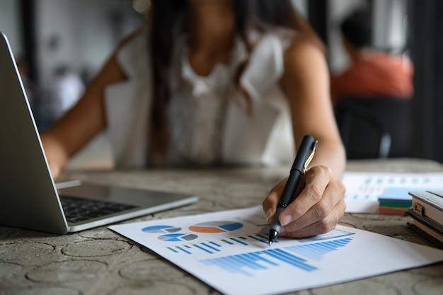 Gli uomini d'affari femminili stanno controllando i grafici dei dati e stanno utilizzando il computer portatile. puntò la penna sul grafico di fronte.