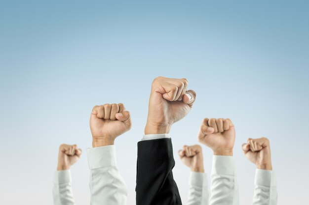 Gli uomini d'affari hanno alzato le mani il successo.