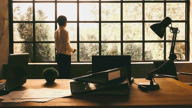 Gli uomini d'affari hanno guardato fuori dalla finestra per trovare l'ispirazione