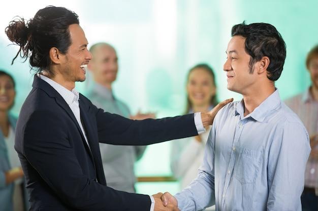 Gli uomini d'affari joyful stringono la mano dopo riunioni