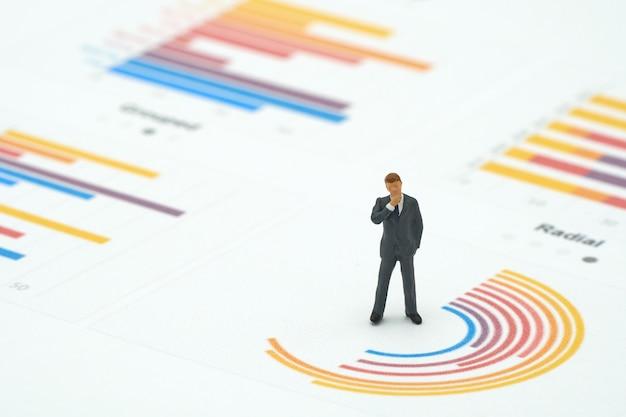 Gli uomini d'affari miniatura della gente analizzano la condizione sul grafico del cerchio