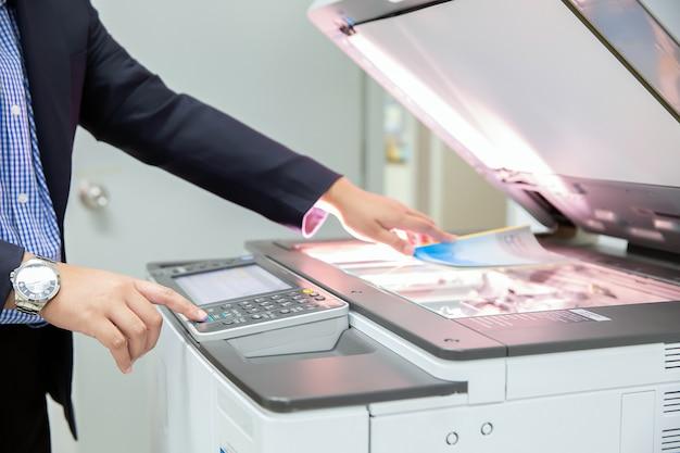 Gli uomini d'affari premono il pulsante sul pannello della fotocopiatrice.
